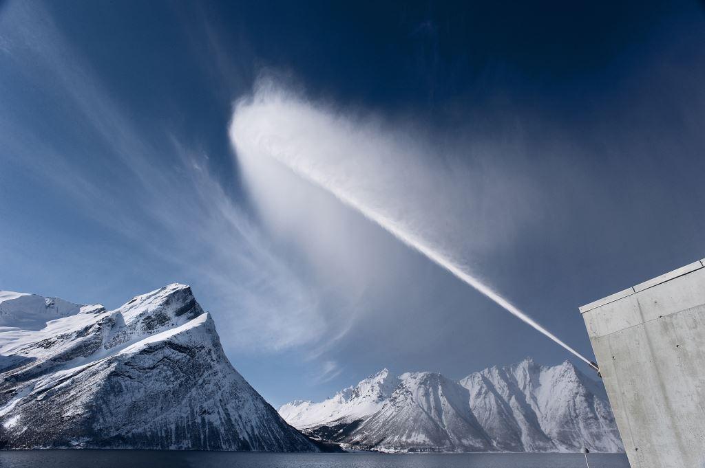 vann fra en vannkanon med snødekte fjell i bakgrunnen