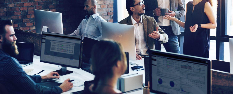 Bilde fra et kontor der flere ansatte sitter og jobber med Xledger på PCer