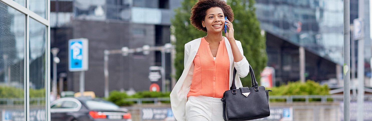 Dame i byen går å snakker i telefon og er fornøyd med at hun nettopp har fått lønn
