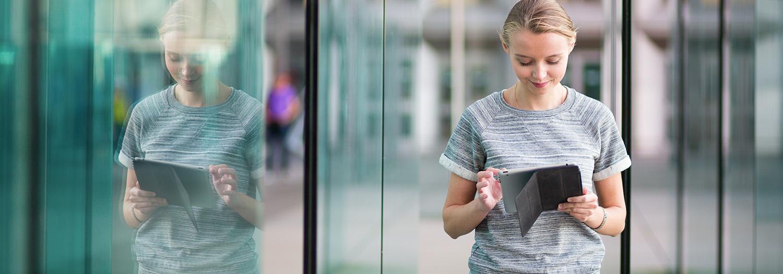 Blond dame står ved en glassvegg og sjekker sin iPad. Har full kontroll på innkjøp og logistikk