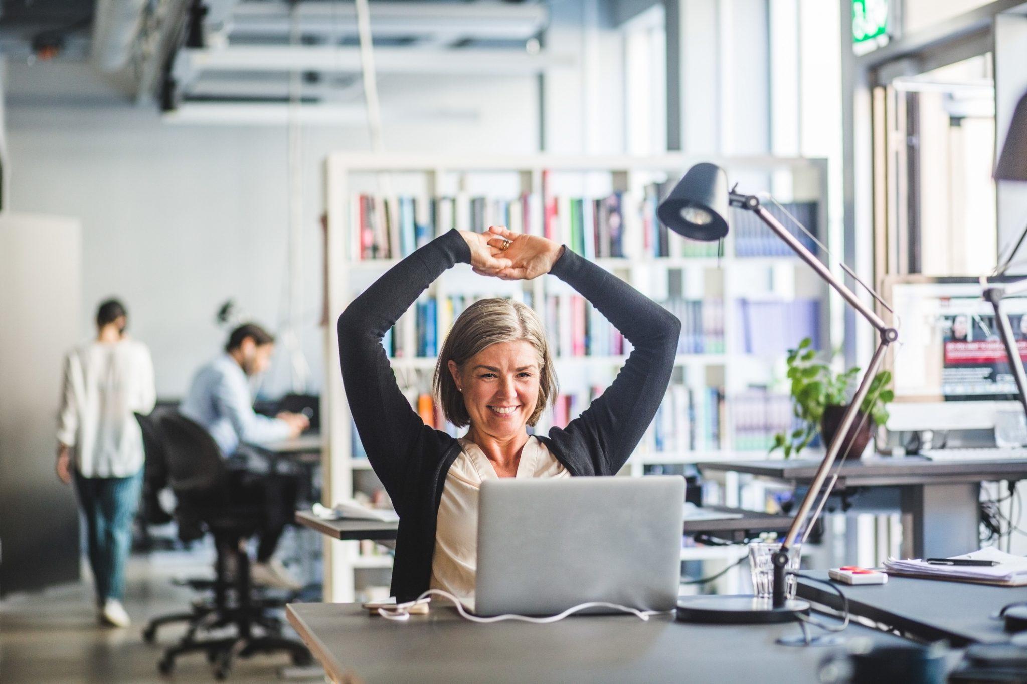 Dame ved kontorpult med PC strekker hendene over hodet etter at hun er ferdig med ordre og fakturering
