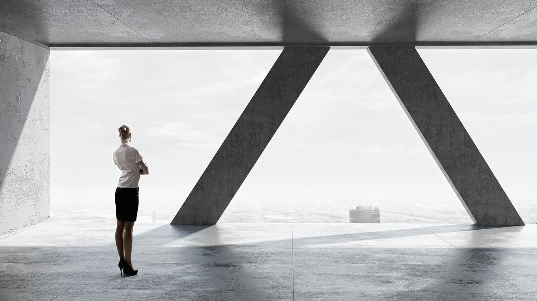 Dame står ved to betongsløyler og ser ut fra toppen av en bygning