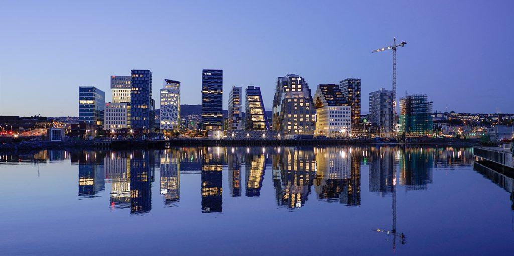 Et bilde av Barcode i Oslo tatt om kvelden. Eiendommene speiler seg i vannet