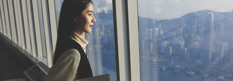 Kvinne står ved et vindu i en skyskraper og har full kontroll over byen under seg. Har siste rapport under armen