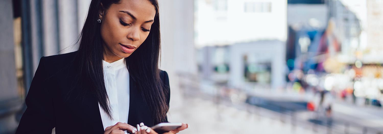 Kvinnelig konsulent som står ved et vindu og sjekker sin iPhone