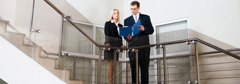 Mann og dame i en trapp som driver kontroll og overvåking av anleggsregister