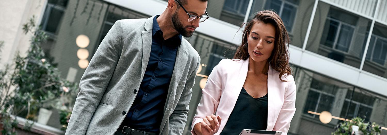 Mann og dame utenfor et kontrobygg sjekker prosjektregnskap på en iPad