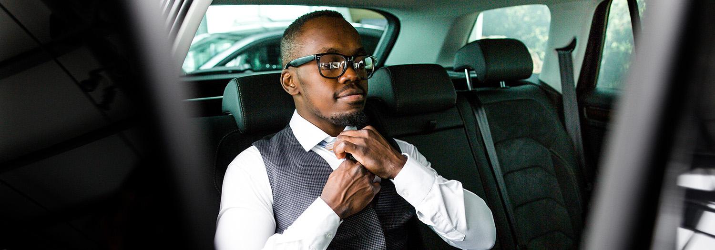 Mann som sitter i baksetet på en bil. Kan skrive timer å utlegg på vei til jobbmøte.