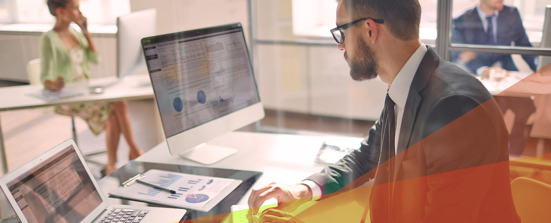 Mann som sitter ved en kontorpult og jobber med regnskap i Xledger på en PC