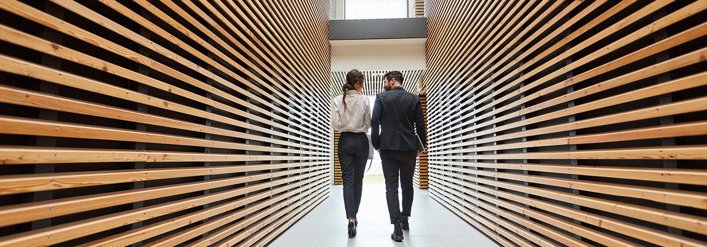 Profesjonell mann og dame som går nedover en moderne gang mens de diskutererer arbeidsflyt i regnskap og økonomi
