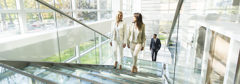 To damer går opp en glasstrapp i et moderne bygg mens de snakker om tilleggstjenester