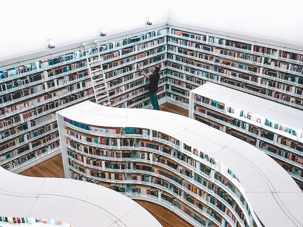 Mann putter inn bøker i en stor bokhandel