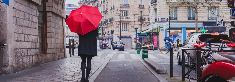 Ambasiøs dame med rød paraply gåt nedover fortauet i en by. Tenker på hvorfor hun skal velge Xledger.