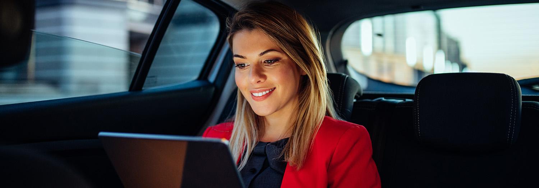 Dame som skroller på iPad. Automatisert bank og betaling. Sitter å smiler i baksetet på en bil