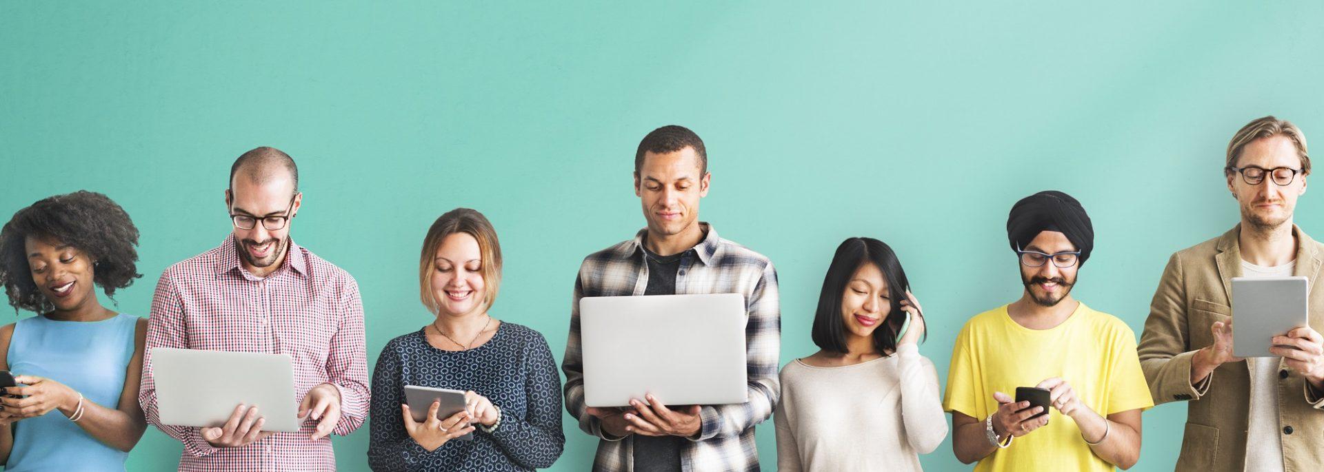personer langs vegg med mobiler og PC