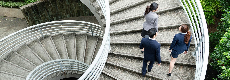 To damer og en mann går opp en trappsom får i sirkler.