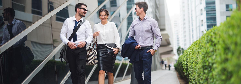 To menn og ei dame går ved siden av en glassbygning veldig fornøyd med å ha et alt i ett system