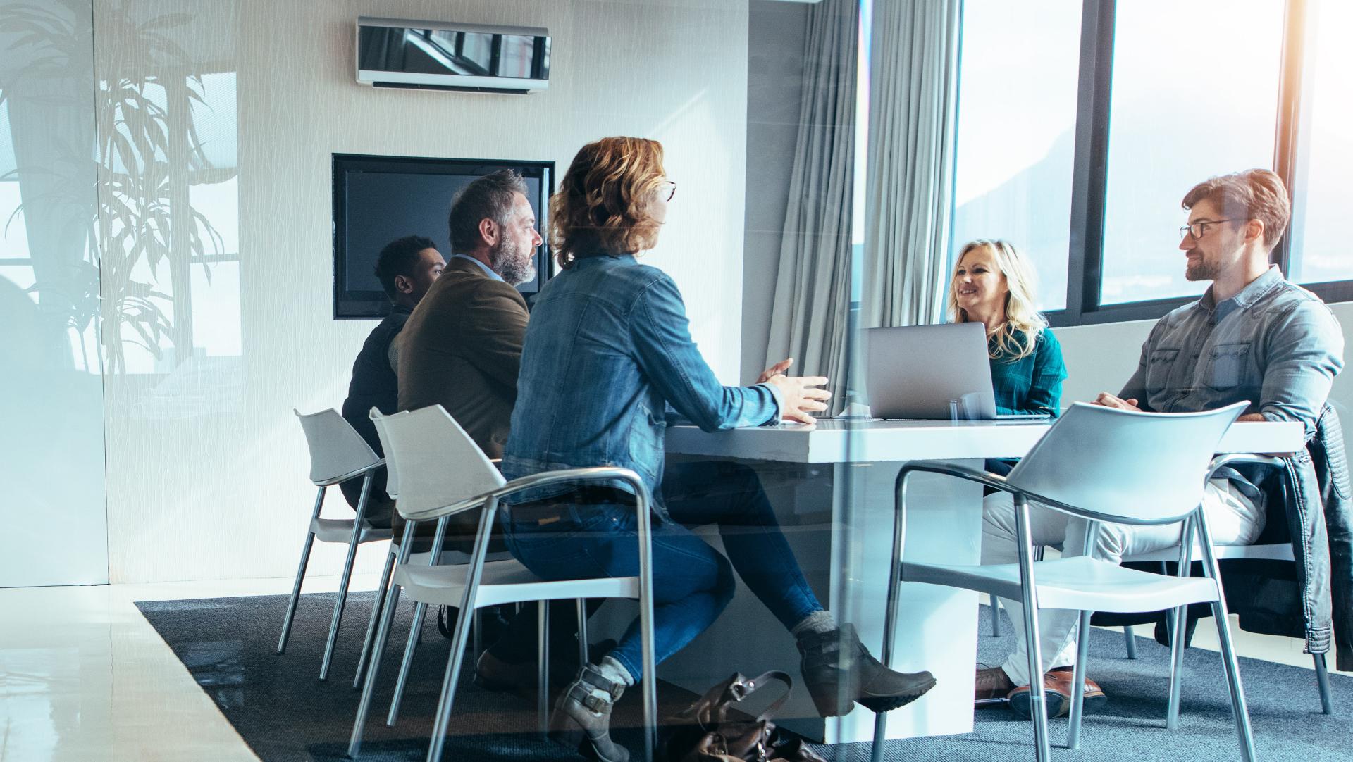 Mennesker i møte rundt et bord som diskuterer implementering i Xledger