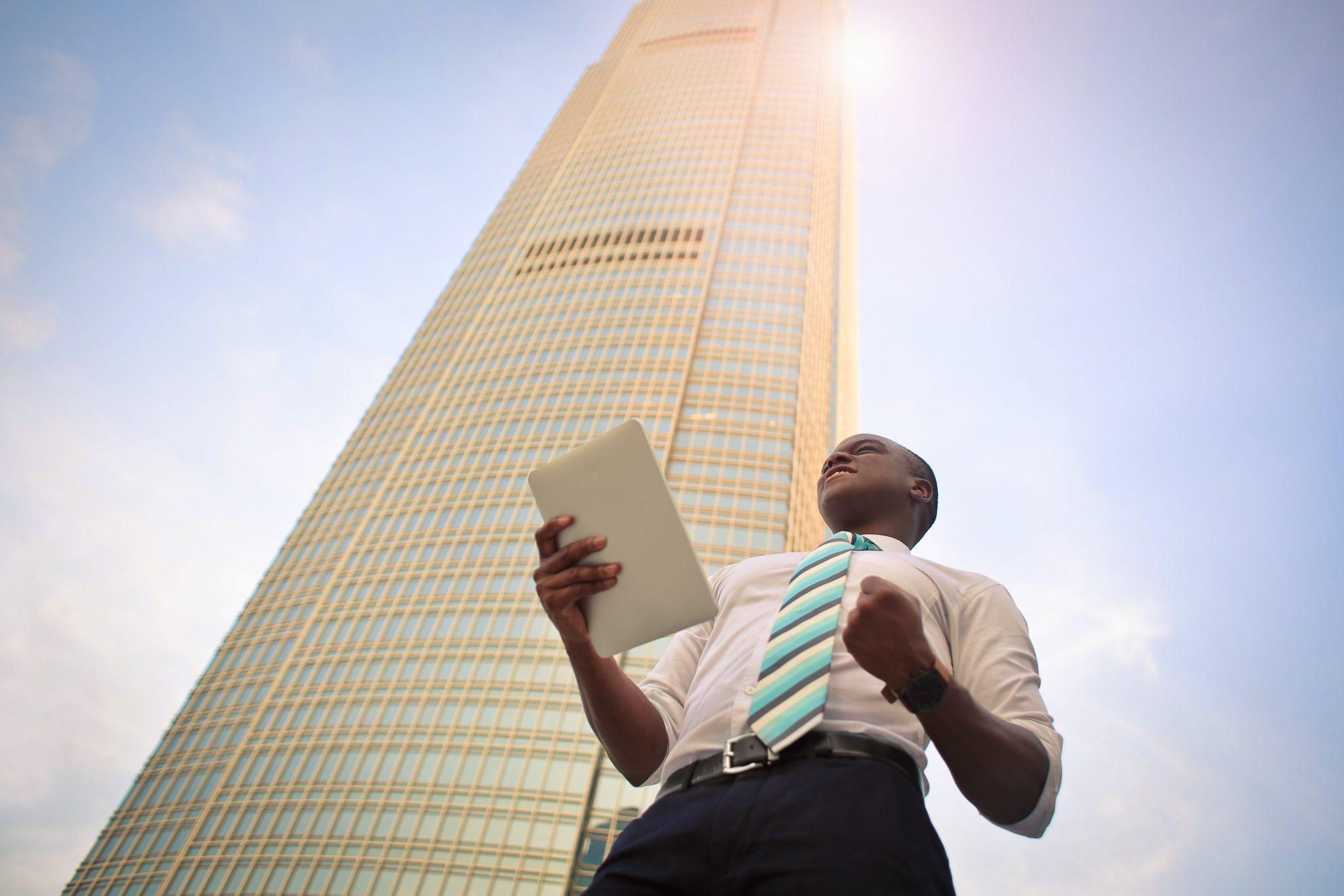 Forretningsmann forann et stort kontorbygg med store og komplekse virksomheter