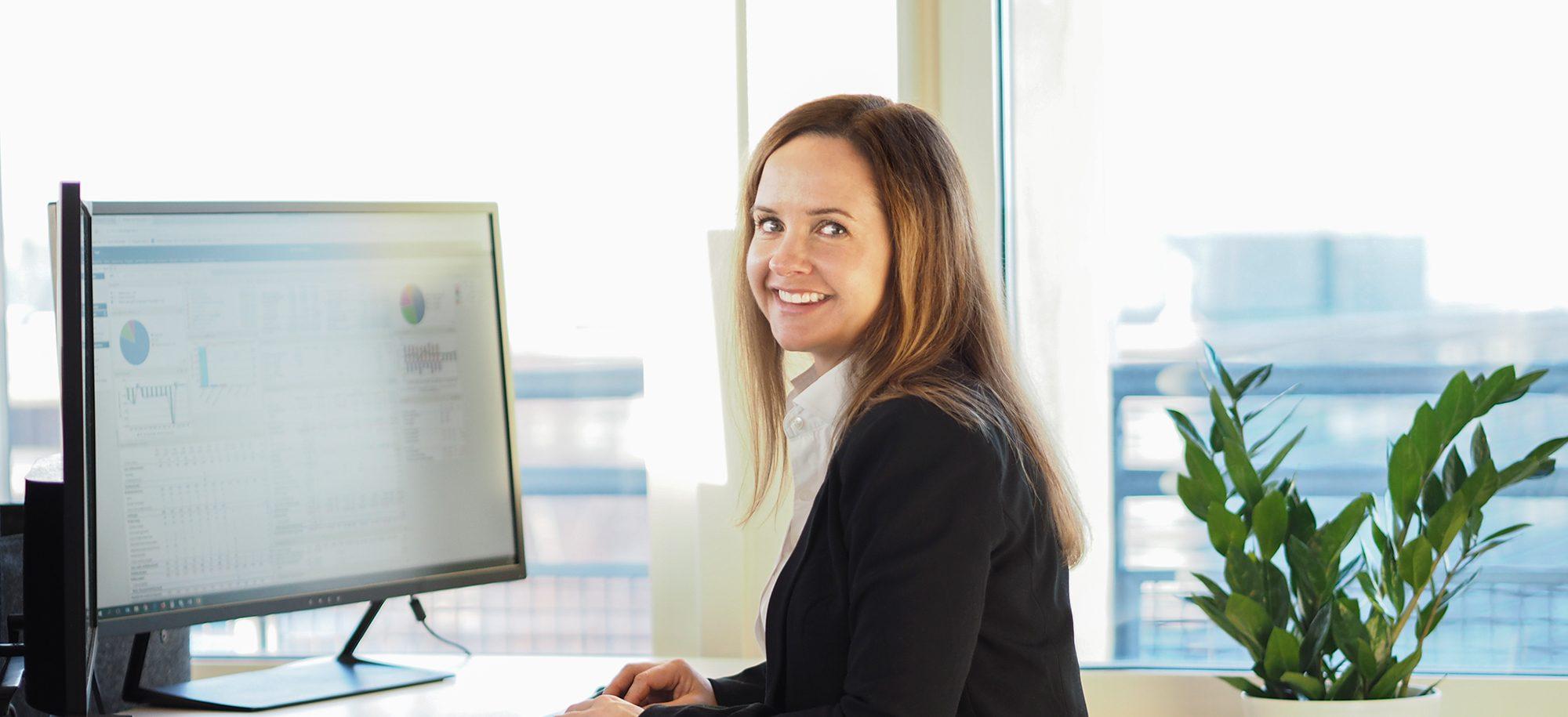 Smilende kvinnelig Functional Expert ved datamaskin ser mot kamera