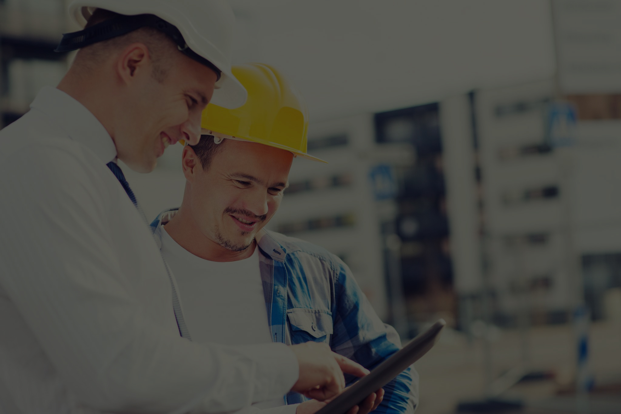 To CFOer i entreprenørbransjen står smilende ute på en arbeidsplass og ser på et nettbrett sammen