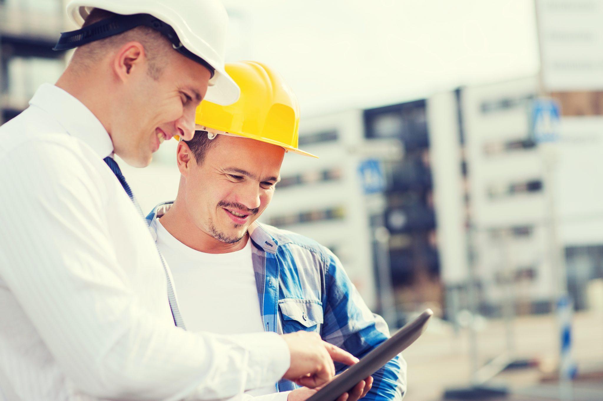Bilde av to mannlige CFOer i entreprenørbransjen som står å ser på en tablet ute på en byggeplass