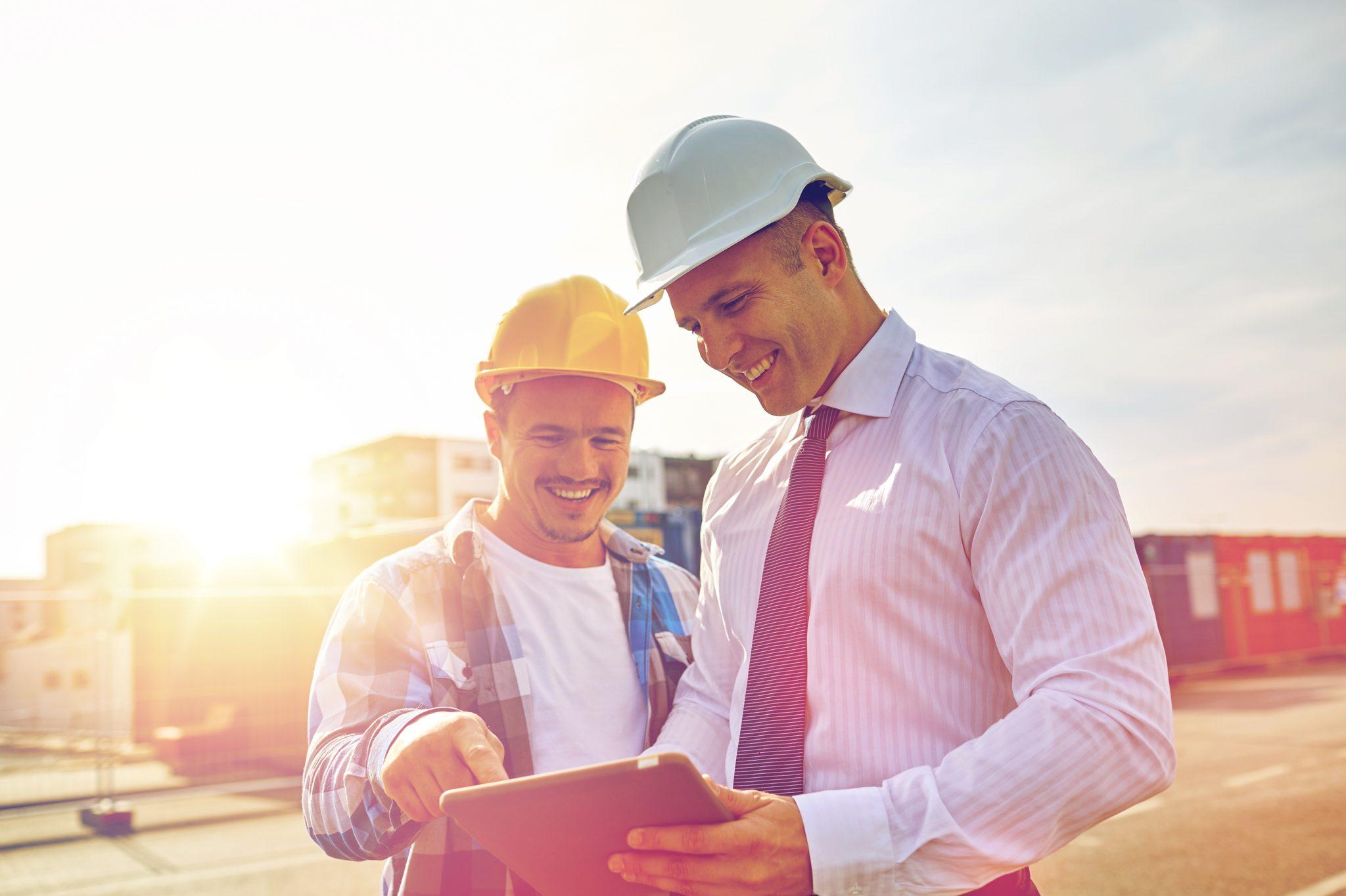 Bilde av to CFOer i entreprenørbransjen som står ute å ser på et nettbrett