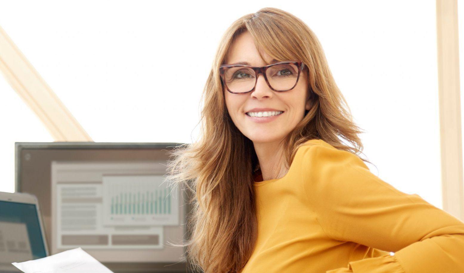 En Kvinnelig Moderne Controller I Gul Genser Sitter Foran PCen Og Ser Rett I Kameraet