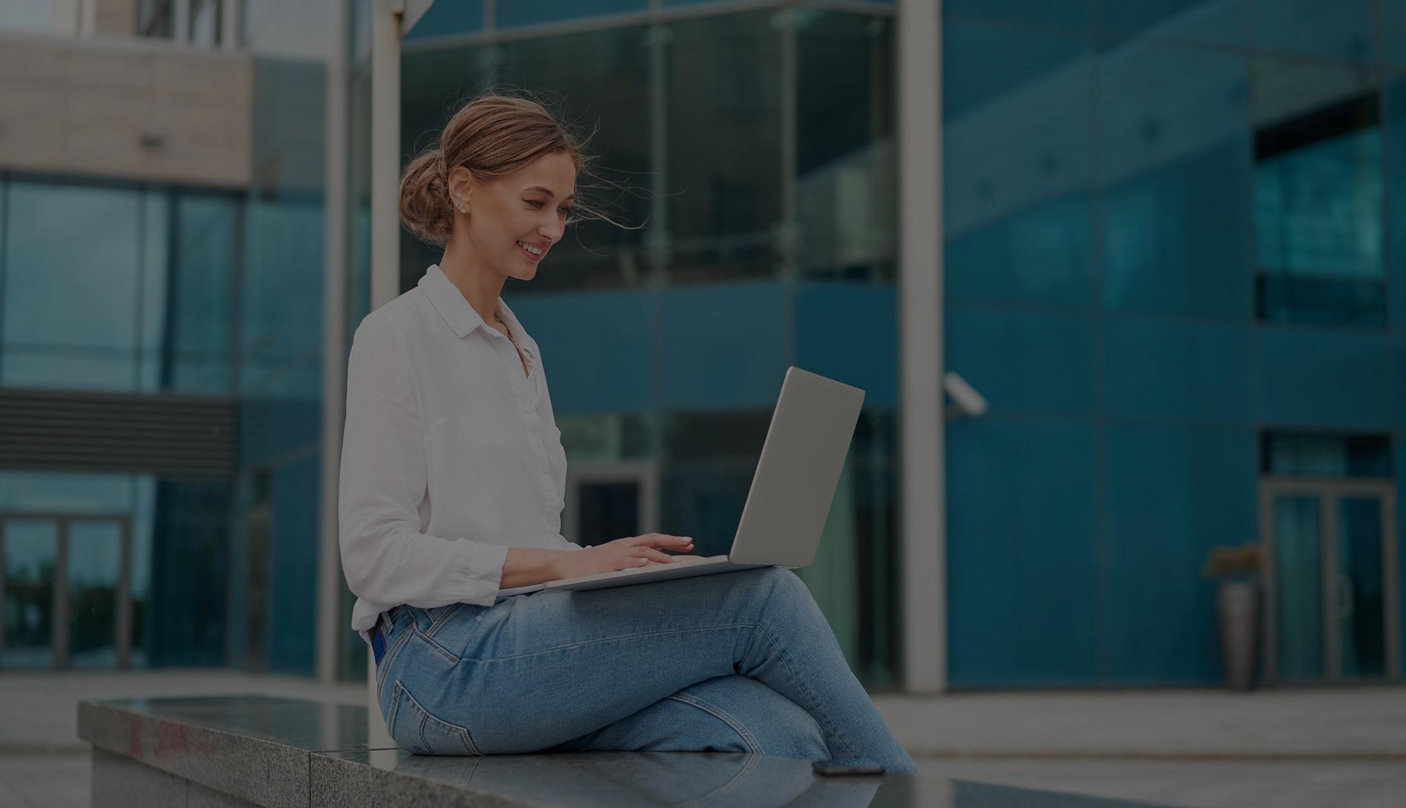 Kvinnelig CFO i eiendomsbransjen sitter ute å jobber på sin laptop