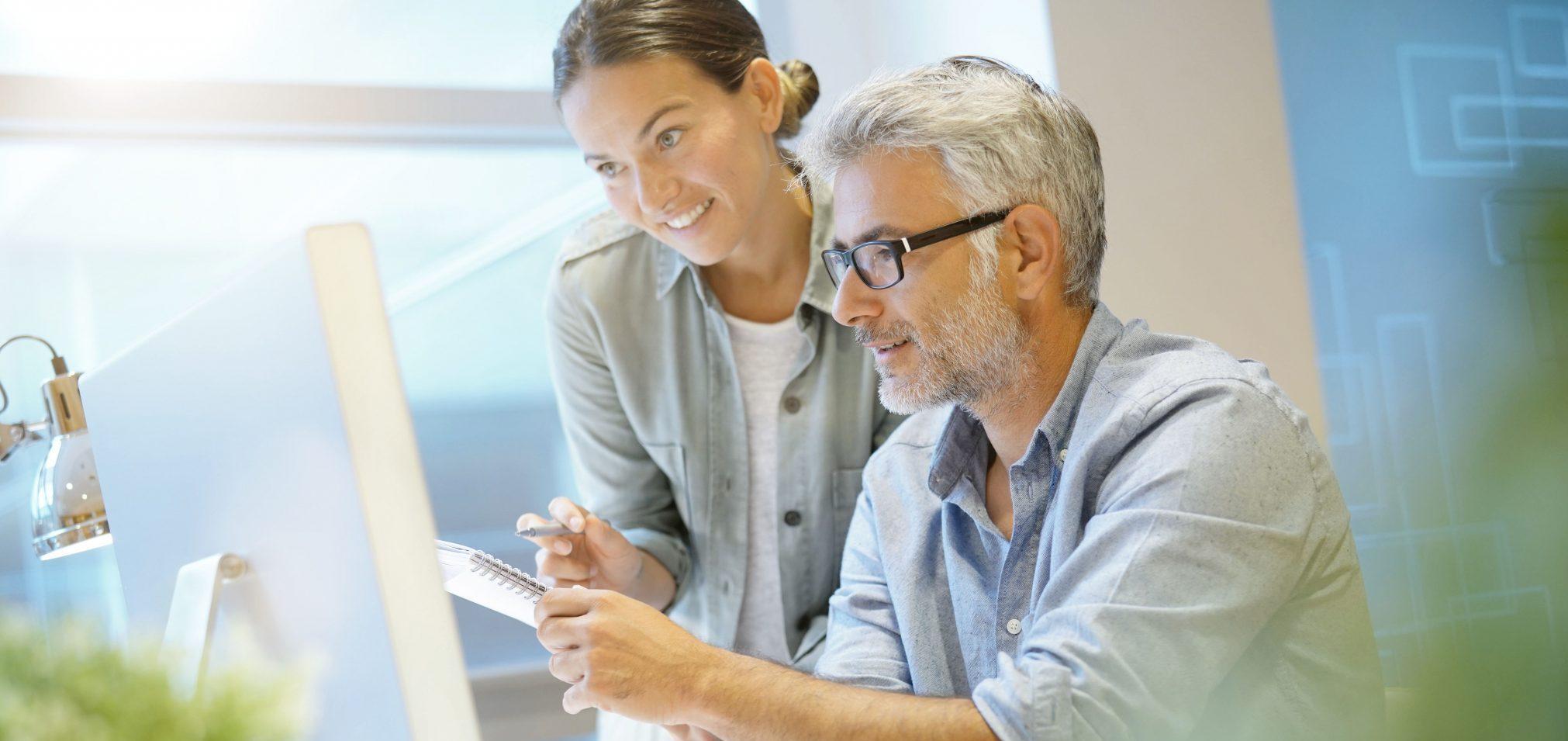 To ansatte som har fokus på bærekraft står ved siden av hverandre på kontoret og ser på en felles dataskjerm