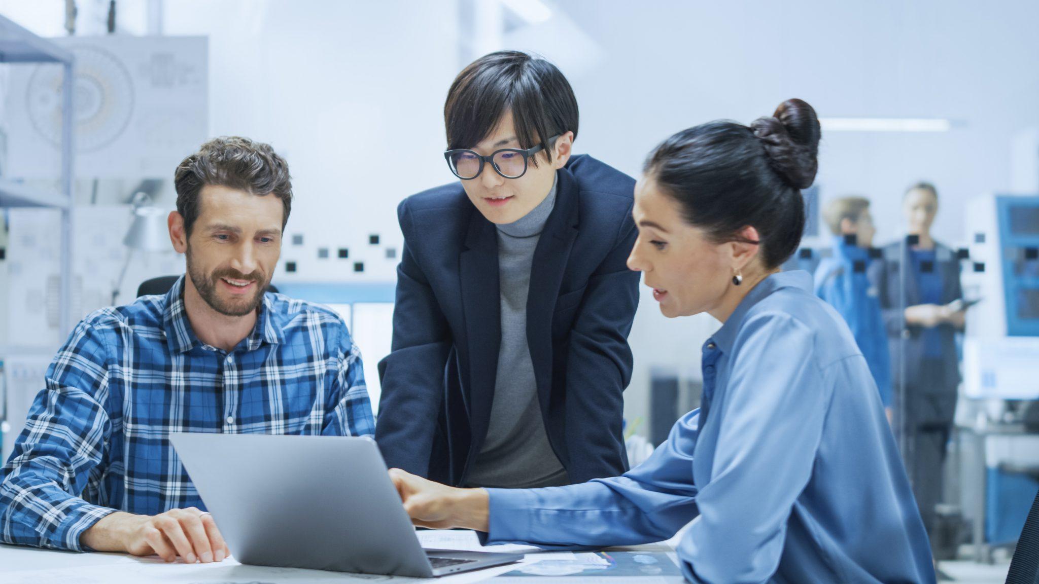 Tre entreprenører som har lyktes med sin digitalisering og digital endring ,står ved et bord å ser på en PC skjerm.