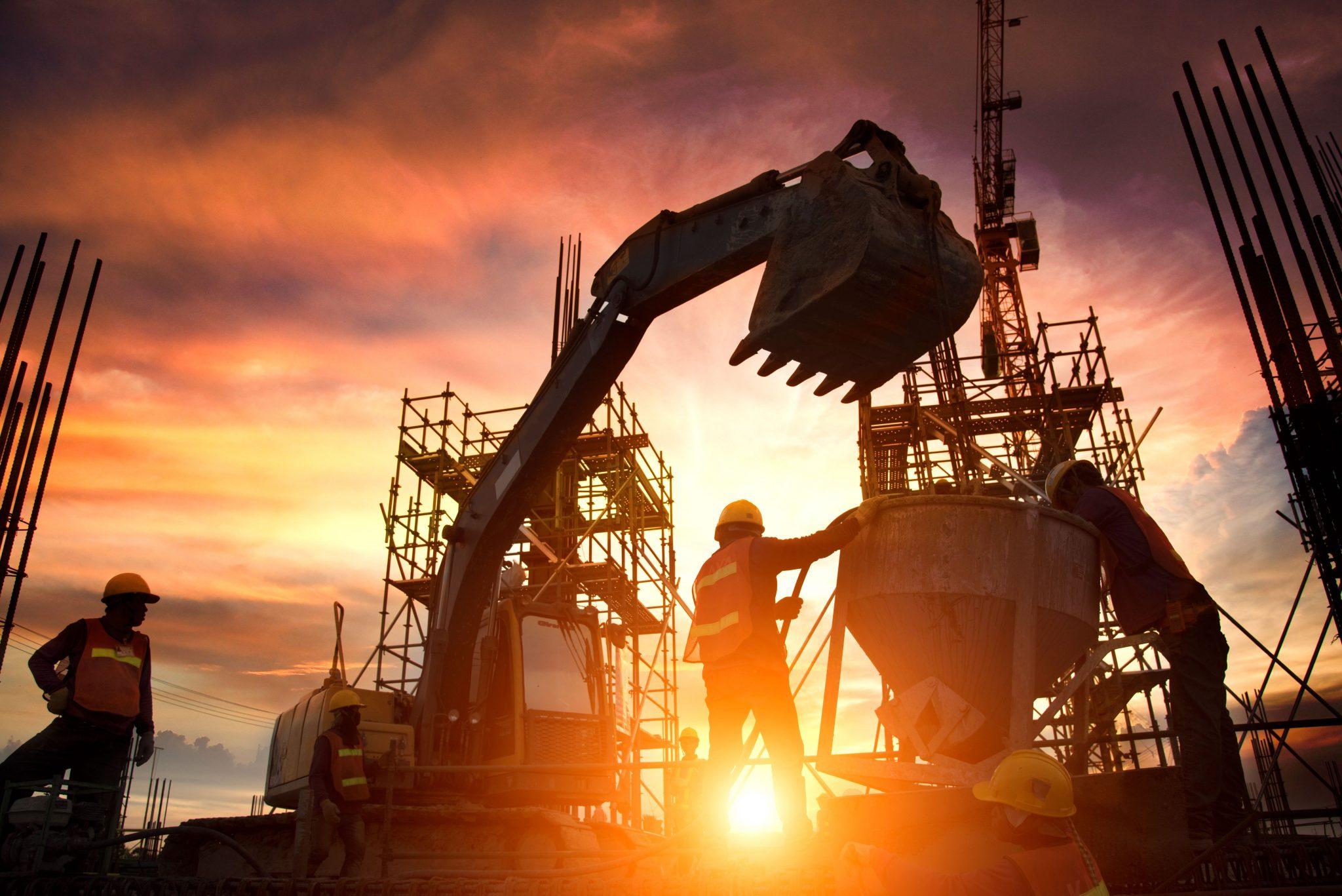Entreprenørbransjen i aksjon på byggeplass i solnedgang