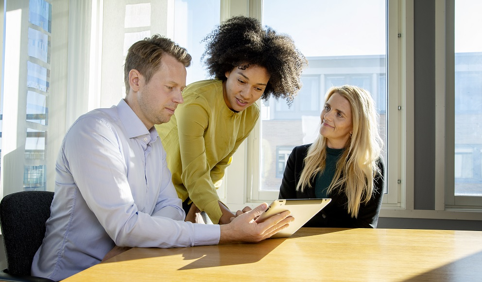 En mann og to damer som jobber ved et bord